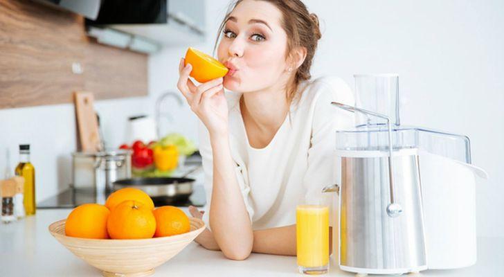 Девушка делает апельсиновый сок